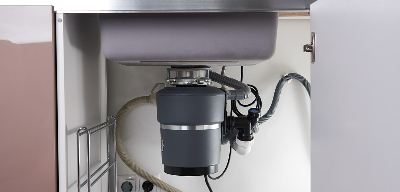 Garbage disposal system installed under a kitchen sink in a residential property.